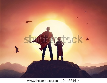 Happy loving family. Father and his daughter playing outdoors. Daddy and his child girl in an Superhero's costumes. Royalty-Free Stock Photo #1044226414