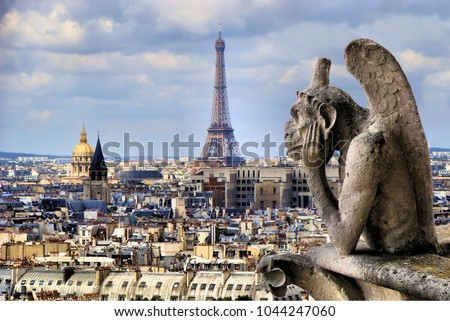 Famous Notre Dame gargoyle overlooking the Paris cityscape with Eiffel Tower