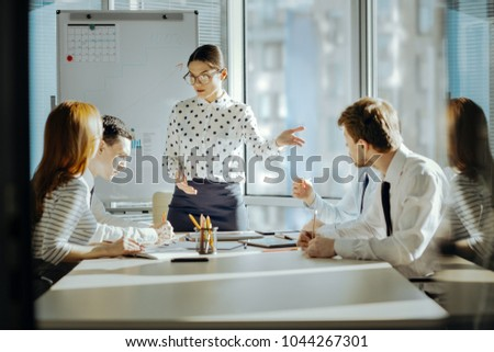 Good psychologist. Pleasant young female boss having a meeting with her employees and trying to solve a conflict between them #1044267301