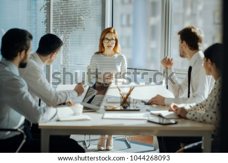 Fruitful collaboration. Charming female boss sitting at the head of the table with her employees and developing a project plan together with them #1044268093