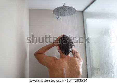 Man taking a shower washing hair under water falling from rain showerhead. Showering person at home lifestyle. Young adult body care morning routine. Royalty-Free Stock Photo #1044283534