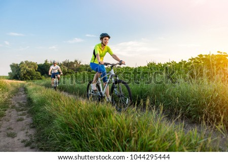 young man and woman are driving their bicycles on their way to the field in the summer. #1044295444