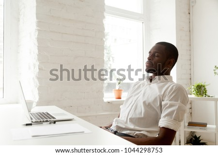 African american man relaxing after work breathing fresh air sitting at home office desk with laptop, black relaxed entrepreneur meditating with eyes closed for increasing productivity at workplace #1044298753