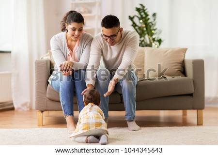 family, parenthood and people concept - happy mother, father with and daughter crawling on at home #1044345643