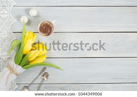 Yellow tulips, chocolate and candies on a white wooden table #1044349006