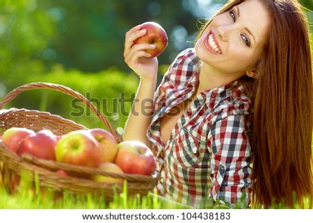 Beautiful woman in the garden with apples #104438183