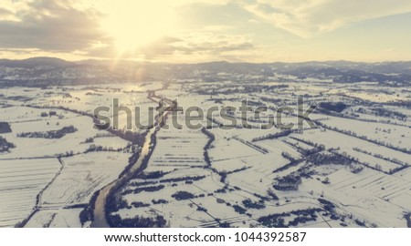 Aerial view of river flowing through snow covered countryside at sunset. #1044392587