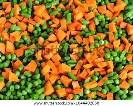Sliced vegetables before baking on the Pan for baking. Carrots, green peas, green beans. The concept of a healthy diet. #1044402058