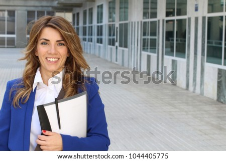 Mid adult businesswoman holding file at work  Royalty-Free Stock Photo #1044405775