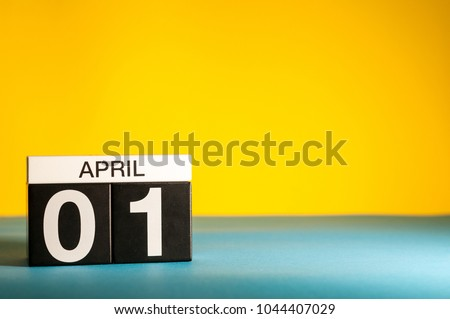 April 1st. Day 1 of april month, calendar on table with yellow background. Spring time, empty space for text Royalty-Free Stock Photo #1044407029
