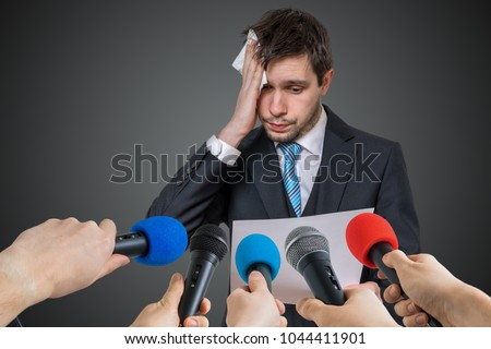 Nervous man is afraid of public speech and sweating. Many microphones in front. Royalty-Free Stock Photo #1044411901