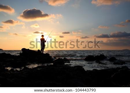 Man fishing in last rays of sunlight on sea shore,Thailand #104443790