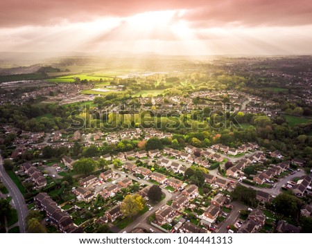 Sun bursting through clouds over traditional British houses with countryside in the background. Dramatic lighting and warm colours to give a homely effect. Royalty-Free Stock Photo #1044441313