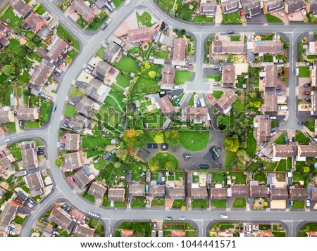 Aerial view of traditional housing estate in England. Looking straight down with a satellite image style, the houses look like a miniature village Royalty-Free Stock Photo #1044441571