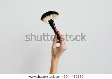 makeup brush in hand on a white background #1044452980