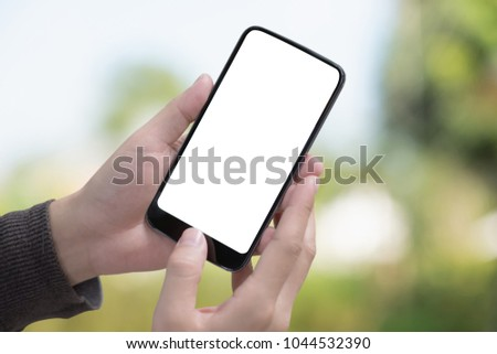Male hand holding smartphone at park. Blank screen mobile phone for graphic display montage #1044532390