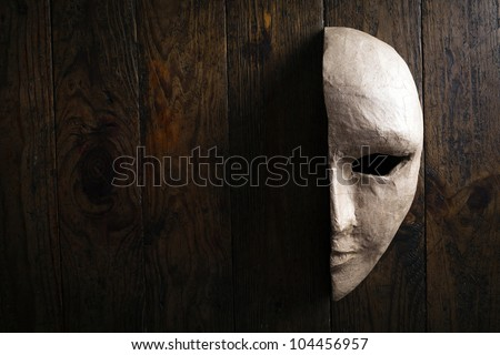 Half of the paper masks on a wooden background #104456957
