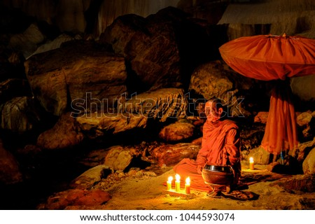 Kanchanaburi, Thailand - July 15, 2011:Buddhist monk sitting with alms bowl, lighten candle and long-handles umbrella to do individual meditation in the cave in national park in Kanchanaburi, Thailand #1044593074
