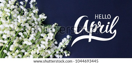 Hello April hand lettering card. Spring lily of the valley flowers on dark blue background. Royalty-Free Stock Photo #1044693445