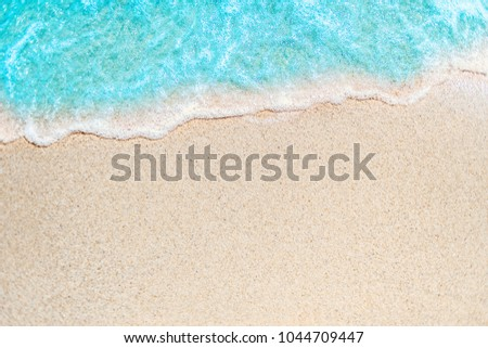 Soft wave of blue ocean on sandy beach with copy space fr text. Summer Background. #1044709447
