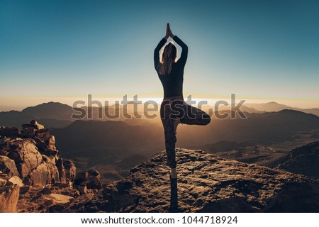 Woman does yoga exercises on edge of cliff on Mount Sinai against background of beautiful sunrise in Egypt. #1044718924