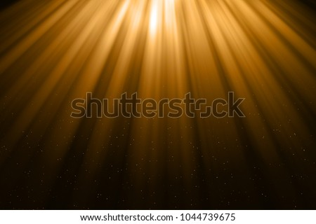 christmas gold gradient sparkle glitter dust particles from top on black background with bokeh flowing and ray light, golden holiday happy new year and valentine day love, relationship concept Royalty-Free Stock Photo #1044739675
