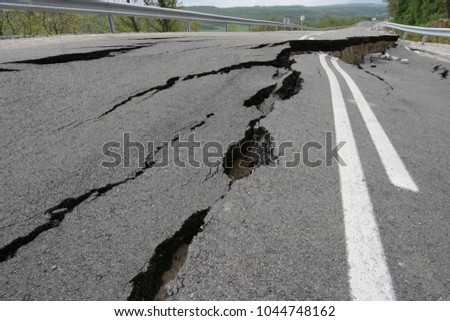 Road collapses with huge cracks. Earthquake. International road collapsed down after bad construction. Damaged Highway Road. Asphalt road collapsed and fallen.  Royalty-Free Stock Photo #1044748162