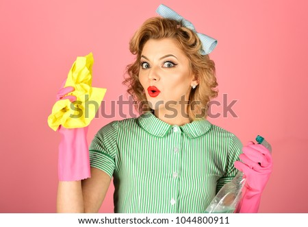 Pinup woman hold soup bottle, duster. Housekeeper in uniform with clean spray, duster. Cleaning, retro style, purity. Cleanup, cleaning services, wife, gender. Retro woman cleaner on pink background. #1044800911