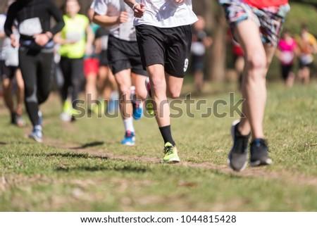 Marathon running race, people feet on grass road #1044815428