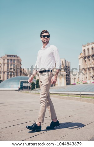 Vertical full-length portrait of serious handsome attractive virile masculine pensive foreigner wearing formal outfit white shirt beige pants walking in city center architecture houses background #1044843679
