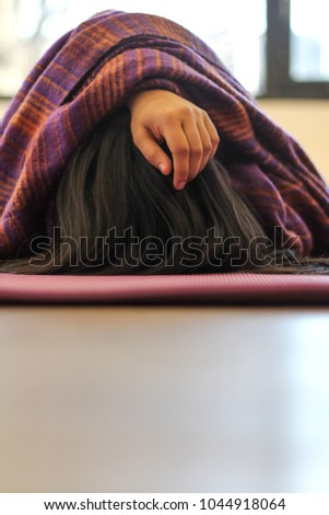 Young south asian woman in pranayama after a yoga class with blanket over head #1044918064