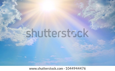 Miraculous Heavenly Light -  Blue sky, fluffy clouds and a beautiful warm orange yellow sun beaming down radiating depicting a holy entity   Royalty-Free Stock Photo #1044944476