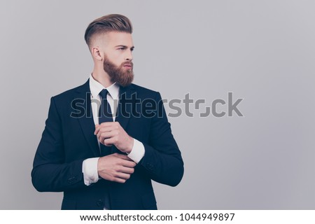 Portrait of handsome attractive neat elegant confident serious concentrated rich luxurious virile masculine boss chief fixing cuff-links on sleeve looking aside profile isolated on gray background #1044949897