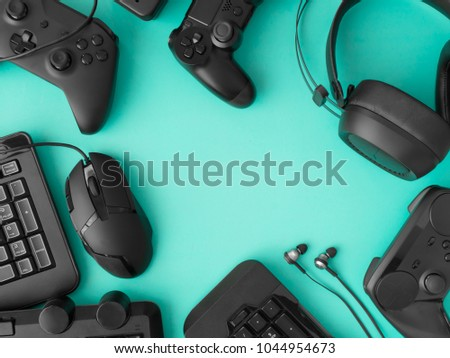 gamer workspace concept, top view a gaming gear, mouse, keyboard, joystick, headset on green table background with copy space.