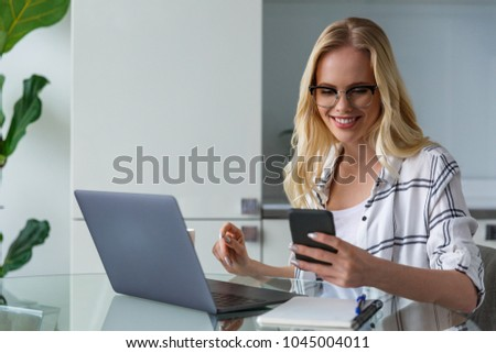 smiling young woman holding smartphone and using laptop while working at home  #1045004011
