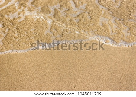 Soft waves with foam of ocean on the sandy beach background #1045011709
