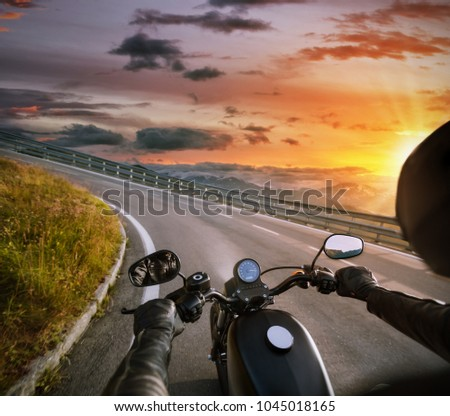 POV of motorbiker holding steering bar, riding in Alps in beautiful sunset dramatic sky. Travel and freedom, outdoor activities #1045018165