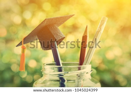 Education is the most powerful weapon or knowledge is power concept : Black graduation cap or hat with a tassel on a pencil in a clear glass jar / bottle, silver pencil with white rubber points upward #1045024399