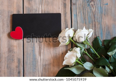 Bouquet of off white spray roses with blank blackboard on a rustic wooden background with free space #1045075939