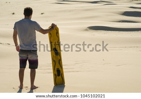 Young man on his back looking at the sand dunes, preparing to practice sandboarding. #1045102021