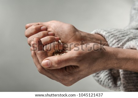 Poor woman holding rice in hands, closeup #1045121437