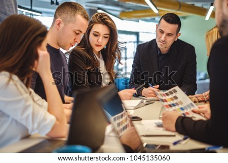 Business People looking at paperwork of a colleague at the meeting #1045135060