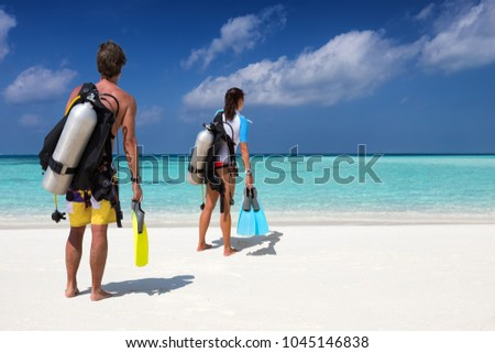 Scuba diver couple with diving equipment on a tropical beach watches the scene #1045146838