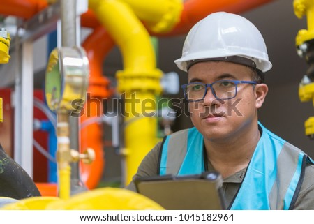 Asian engineer wearing glasses working in the boiler room,maintenance checking technical data of heating system equipment,Thailand people #1045182964