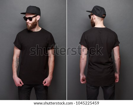 Hipster handsome male model with beard wearing black blank t-shirt with space for your logo or design over gray background Royalty-Free Stock Photo #1045225459