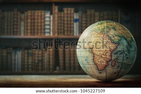 Old globe on bookshelf background. Selective focus. Retro style. Science, education, travel, vintage background. History team. #1045227109