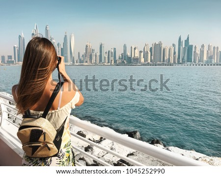 Dubai travel tourist woman on vacation in the Palm Jumeirah taking photo on the camera. Royalty-Free Stock Photo #1045252990