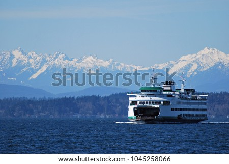 Washington State Ferry cruises in front of Olympic Mountains on approach to Seattle Royalty-Free Stock Photo #1045258066