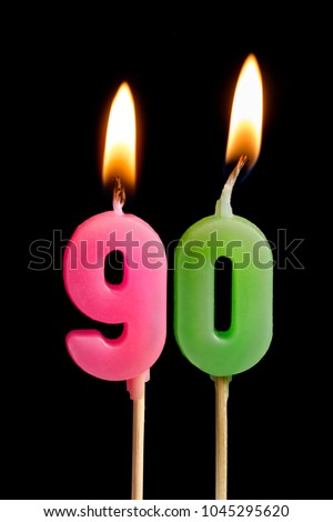 Burning candles in the form of 90 ninety figures (numbers, dates) for cake isolated on black background. The concept of celebrating a birthday, anniversary, important date, holiday