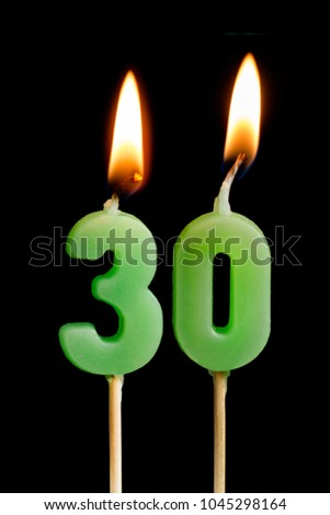 Burning candles in the form of 30 thirty figures (numbers, dates) for cake isolated on black background. The concept of celebrating a birthday, anniversary, important date, holiday
